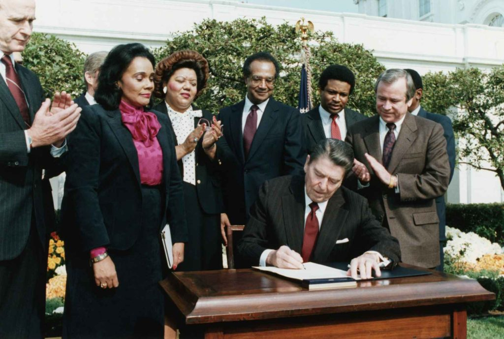In the presence of Coretta Scott King (2nd from left), President Ronald Reagan signs a bill making Martin Luther King Jr.'s birthday a national holiday.